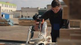 Pracownik jest ubranym budowa gogle i mundur czerni i błękita używać drewnianą tnącą maszynę Mężczyzna ciie drewniane deski zbiory