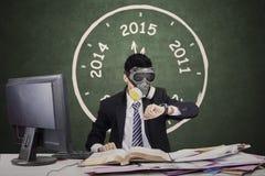 Pracownik jest ubranym maskę gazową i przyglądającego timepiece zdjęcie stock