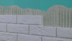 Pracownik kłaść białe cegieł płytki na ścianie zbiory wideo