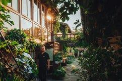 Pracownik kawiarnia w podwórku przeciw tłu typowi drewniani budynki które otaczają greenery, Fotografia Stock