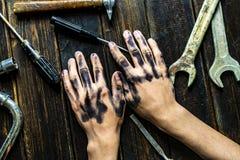 Pracownik klasowej osoby zmroku brudne ręki na drewnianym stole z narzędzia wyposażeniem f zdjęcie stock