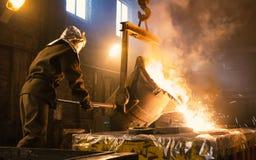 Pracownik kontroluje metalu stapianie w pach Pracownicy działają przy metalurgiczną rośliną Ciekły metal nalewa Obraz Royalty Free