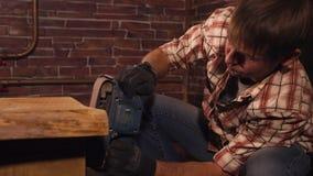 Pracownik który robi powierzchni drewnianego stołu gładcy chwyty wewnątrz wręcza ostrzarza zbiory