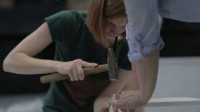 Pracownik młoda piękna kobieta zbiera drewnianą budowę podczas gdy siedzący na podłoga zbiory