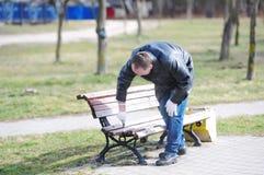 Pracownik maluje ławkę w ulicie fotografia royalty free