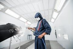 Pracownik maluje samochodowe czarne puste części w specjalnym garażu, będący ubranym kostiumową i ochronną przekładnię fotografia stock