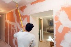 Pracownik maluje sufit farba rolownikiem w korytarzu, przemodelowywa, odświeżanie mieszkanie jest inder budową obrazy stock