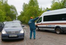 Pracownik ministerstwo sytuacje awaryjne Rosja reguluje ruchu samochody na drodze blisko Moskwa Zdjęcia Royalty Free