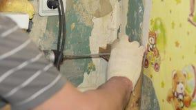 Pracownik musztruje ścianę z elektrycznym świderem, naprawy w domu zdjęcie wideo