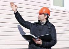 Pracownik na budowie w zim spojrzeniach przy rysunkiem Obraz Royalty Free
