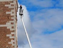 Pracownik na powietrznej platformie czereśniowy zbieracz, utrzymuje fasadę budynek Niebieskie niebo z puszystymi chmurami na back zdjęcia royalty free