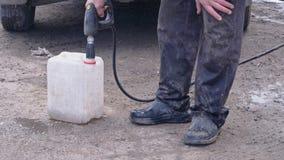 Pracownik nalewa paliwo w upadki i kanister przypadkowo zbiory