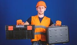 Pracownik, naprawiacz, repairman, budowniczy wybiera wyposażenie dla pracy na rozważnej twarzy Mężczyzna w hełmie, ciężkiego kape zdjęcia stock