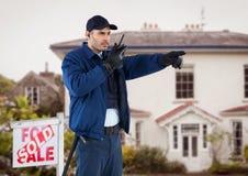 Pracownik ochrony opowiada na walkie talkie i gestykuluje przeciw domowi podczas gdy stojący znak deską Zdjęcia Royalty Free