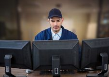 Pracownik ochrony patrzeje ekrany w zamazanym biurowym tle Obrazy Royalty Free