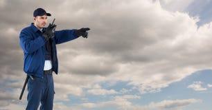 Pracownik ochrony używa radio przeciw chmurnemu niebu Obraz Stock