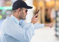Pracownik ochrony wskazuje z walkie talkie przeciw rozmytemu centrum handlowemu Obrazy Royalty Free