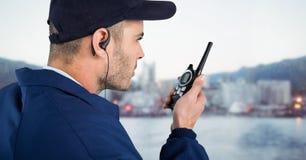 Pracownik ochrony z nakrętki i walkie talkie przeciw rozmytej linii horyzontu Obrazy Stock