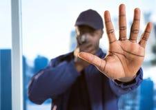 Pracownik ochrony z walkie talkie i ręka w przodzie przeciw rozmytemu nadokiennemu pokazuje miastu Zdjęcie Royalty Free
