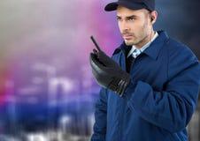 Pracownik ochrony z walkie talkie przeciw rozmytej ścianie z miasta nakreśleniem Zdjęcie Stock