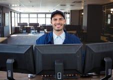 pracownik ochrony za ekranami, ono uśmiecha się W biurze Obraz Royalty Free