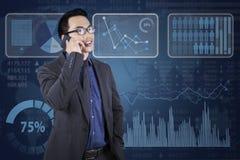 Pracownik opowiada na telefonie z pieniężnym wykresem Zdjęcia Stock