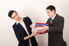 Pracownik otrzymywa wiele kartoteki od jego szczęśliwego szefa. Obraz Royalty Free