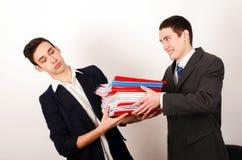 Pracownik otrzymywa wiele kartoteki od jego szczęśliwego szefa. Obrazy Stock