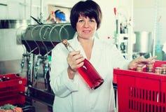 Pracownik pakuje wino butelki przy iskrzastego wina fabryką Zdjęcia Stock