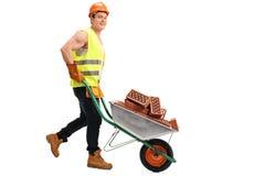 Pracownik pcha wheelbarrow z cegłami fotografia stock