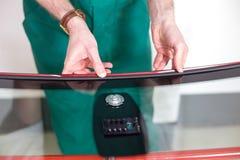 Pracownik pieczętuje dla windscreen w szklarza warsztatowym narządzaniu Zdjęcie Royalty Free