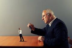 Pracownik pod powiększać - szkło jego szef zdjęcia royalty free