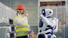 Pracownik pokazuje cyborgowi niektóre gesty kopiować, then dają each inny cześć 4K zbiory