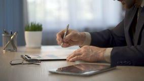 Pracownik porównuje dane na pastylki i papieru wykresach, prezentacja definitywni dane zdjęcie wideo