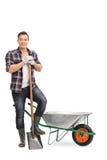 Pracownik pozuje pustym wheelbarrow Fotografia Royalty Free