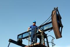 Pracownik pozycja na pompowej dźwigarce Zdjęcia Stock
