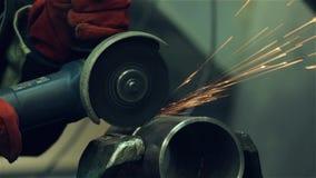 pracownik przetwarza część z szlifierską maszyną zbiory