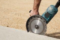Pracownik ręki mienia kąta ostrzarz z diamentu betonu tnącym dyskiem Zdjęcia Stock