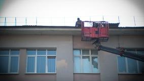 Pracownik rozjaśnia dach od, czyści dachy domy, pracujące użyteczność, spółka zarządzająca i śniegu, lodu i brudu fotografia royalty free