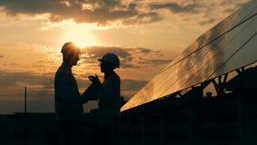 Pracownik rozmowa blisko słońce panel na zmierzchu tle, boczny widok zdjęcie wideo