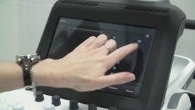 Pracownik służby zdrowia używa ultradźwięku przeszukiwacz Doktorski ` s dotyka na dotyka ekranie Posiadanie sprzęt medyczny zbiory