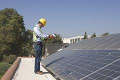 Pracownik Sprawdza panel słoneczny Na dachu Fotografia Royalty Free