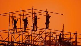 Pracownik sylwetka przy zmierzchów budowniczymi zbiera projekt pracownika budowlanego pojęcia budynku sylwetki mężczyzna zwalniaj zbiory