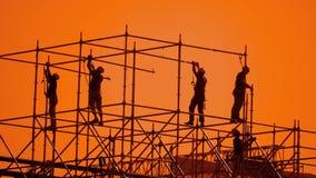 Pracownik sylwetka przy zmierzchów budowniczymi zbiera projekt pracownika budowlanego pojęcia budynku sylwetki mężczyzna zwalniaj zbiory wideo