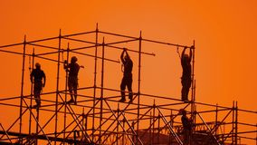 Pracownik sylwetka przy zmierzchów budowniczymi zbiera projekt pracownika budowlanego pojęcia budynku sylwetki mężczyzna grupa zbiory