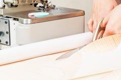 pracownik szwalna produkcja używa nożyce dla ciąć tkanina zdjęcie stock