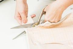 pracownik szwalna produkcja używa nożyce dla ciąć tkanina obraz stock