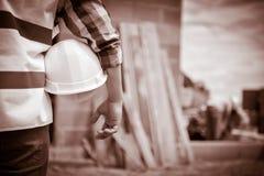 Pracownik trzyma hełm z tłem budowa Fotografia Stock