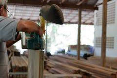 Pracownik trzyma pasowego sander na vertical drewniana deska w ciesielka warsztacie Zdjęcia Stock