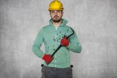 Pracownik trzyma piętaka w jego ręce, ufna postawa obraz stock